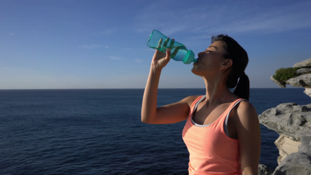 Beautiful latin american woman drinking water after exercising looking at the beautiful sunrise