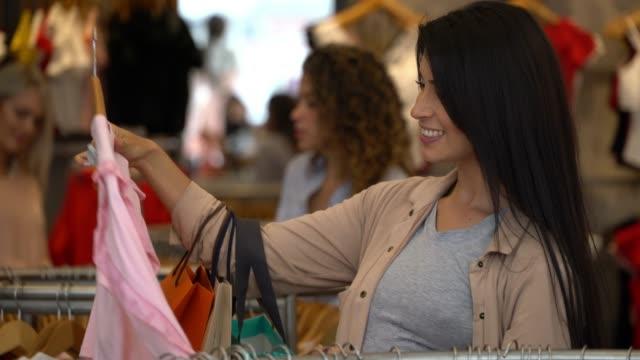 stockvideo's en b-roll-footage met mooie latijns-amerikaanse vrouw kijken naar een shirt op een kleding rek glimlachen - kledingrek