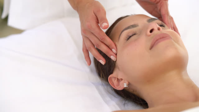 beautiful latin american woman receiving a head massage at a spa - head massage stock videos and b-roll footage