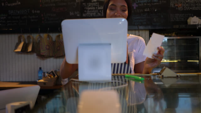 beautiful latin american woman registering an order on the system at a bakery from a paper - ordering stock videos & royalty-free footage
