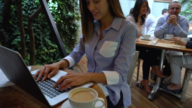 Beautiful latin american woman working on her laptop at a coffee shop looking very happy and smiling