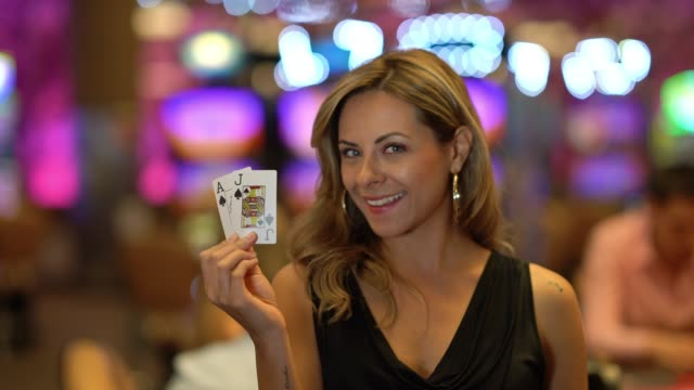 beautiful latin american young woman holding cards while smiling at camera in the casino - casino worker stock videos and b-roll footage