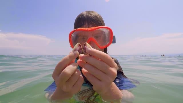 stockvideo's en b-roll-footage met mooie scheutje meisje spelen op het strand in griekenland - vrijetijdsbesteding