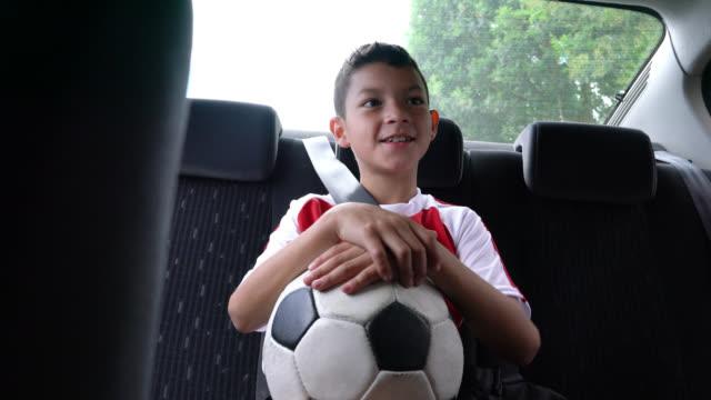 bellissimo bambino che si mette in macchina e si mette la cintura di sicurezza dopo l'allenamento di calcio - ball video stock e b–roll