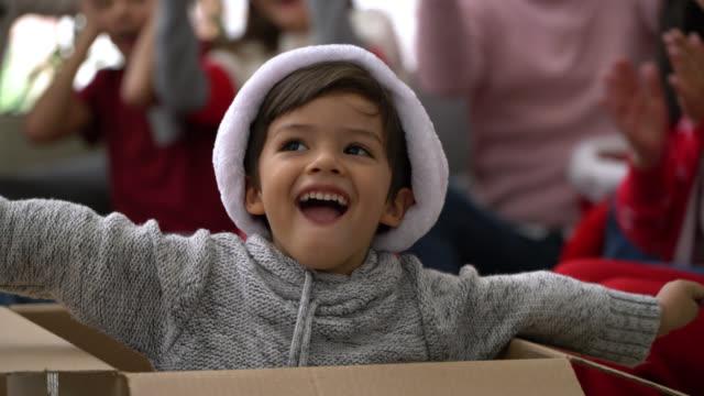 vidéos et rushes de beau petit garçon sortant d'une boîte pendant la célébration de noel à la maison - les bras écartés