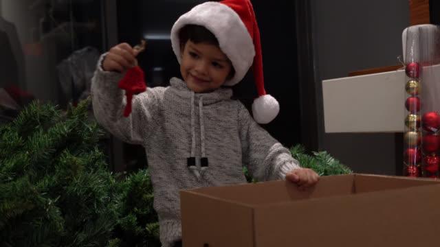 vídeos de stock, filmes e b-roll de rapaz pequeno bonito que toma para fora os ornamento do natal da caixa ao desgastar o chapéu de santa em casa - esfera