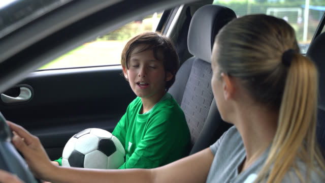 beautiful little boy talking to mom about his soccer practice in the car - drive ball sports stock videos & royalty-free footage