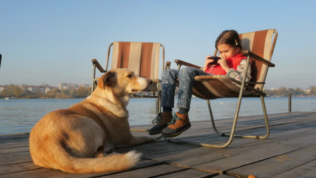 Beautiful little Girl and Yellow Mutt Dog. Living with Pets
