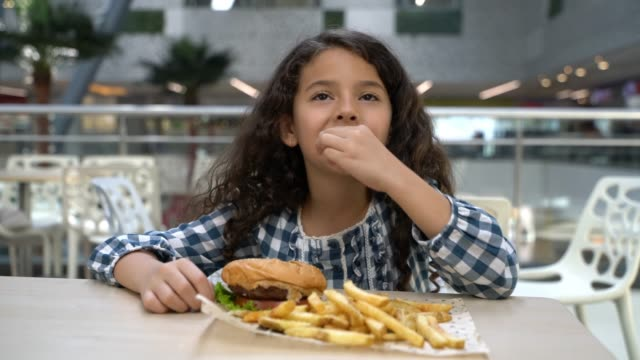 beautiful little girl at the food court mall enjoying a hamburger and fries - food court stock videos and b-roll footage