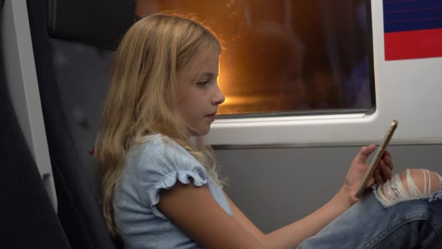 vidéos et rushes de belle petite fille commutant sur le train textant sur son smartphone - passager