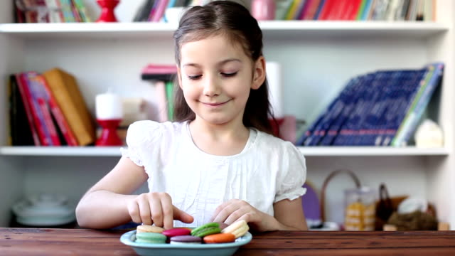 beautiful little girl eating sweet macarons - macaroon stock videos and b-roll footage