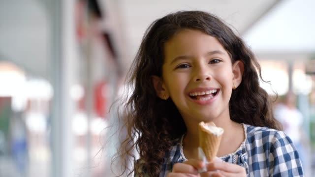 vídeos y material grabado en eventos de stock de hermosa niña disfrutando de un delicioso helado en el centro comercial - centro comercial