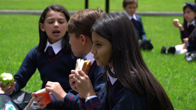 beautiful little girl enjoying a delicious sandwich during her break at school while friends talk at background - school uniform stock videos & royalty-free footage