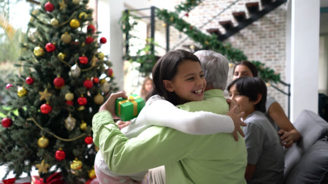 beautiful little girl handing grandfather a christmas present hugging very lovingly while family sits at background - grandfather stock videos & royalty-free footage