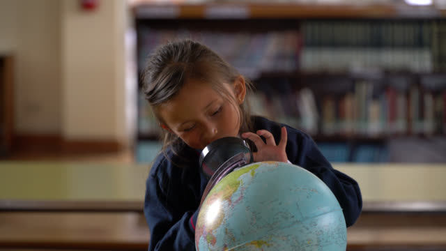 beautiful little girl looking at a global with a magnifying glass and asking a question very confused - confusion stock videos & royalty-free footage