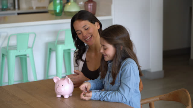 beautiful little girl saving money in her piggy bank and mom sitting next to her talking and smiling - savings stock videos & royalty-free footage