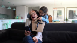 Beautiful little girl surprising her mom while she is sitting on couch using her smartphone with a gift for mother's day