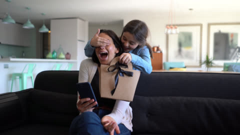 beautiful little girl surprising her mom while she is sitting on couch using her smartphone with a gift for mother's day - mother's day stock videos & royalty-free footage