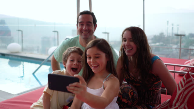 beautiful little girl taking a selfie with her parents and brother enjoying a day at the rooftop pool all smiling - america latina video stock e b–roll