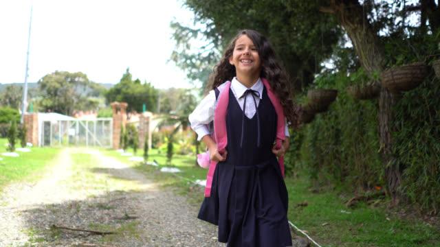 stockvideo's en b-roll-footage met mooi klein meisje wandelen terug naar huis na school glimlachend erg blij - uniform