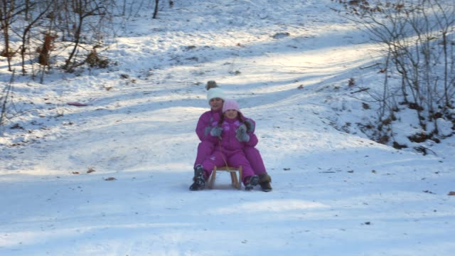 beautiful little girls on sledge having fun - warm clothing stock videos and b-roll footage