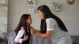 Beautiful loving mother kissing daughter on forehead before leaving to school at home