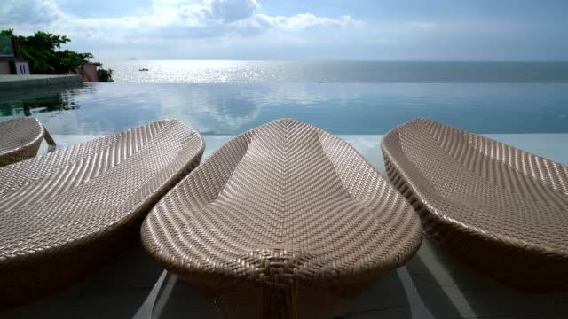 Paraguas de lujo hermoso y silla alrededor de piscina