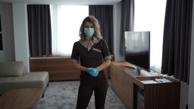 beautiful maid with medical mask and gloves in hotel room - service stock videos & royalty-free footage