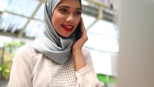 Vackra malaysisk kvinna som bär hijab, prata i telefon i caféet