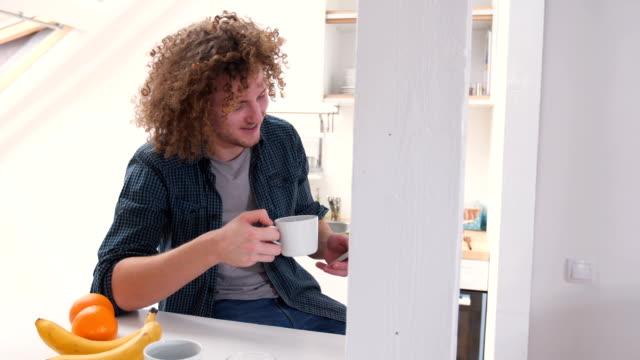 Beautiful man drinking coffee and using phone