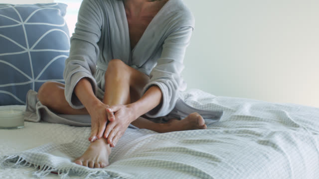 beautiful mature woman applying moisturising cream to her leg. - moisturiser stock videos and b-roll footage