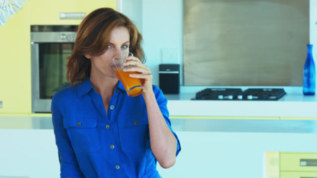 beautiful mature woman drinking an orange vegetable juice. - juice drink stock videos & royalty-free footage