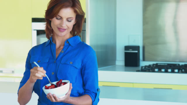 Beautiful mature woman eating a bowl of berries in kitchen.