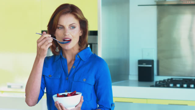 beautiful mature woman eating a bowl of fruit in the kitchen. - fruit bowl stock videos & royalty-free footage