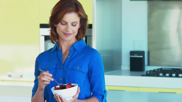 beautiful mature woman eating a bowl of fruit. - fruit bowl stock videos & royalty-free footage