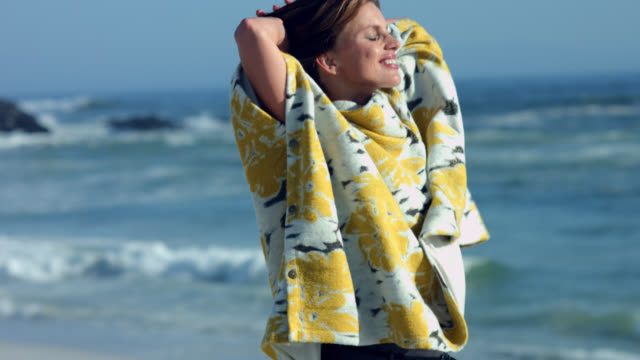beautiful mature woman in a floral poncho at the beach. - woman hands behind head stock videos & royalty-free footage