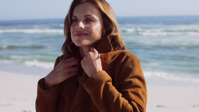 beautiful mature woman in brown suede coat by the sea. - mature adult stock videos & royalty-free footage