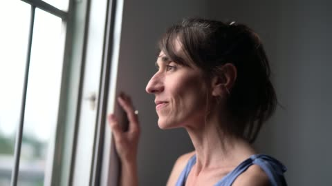 beautiful mature woman looking out of window - hope concept stock videos & royalty-free footage