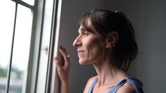 beautiful mature woman looking out of window - daydreaming stock videos & royalty-free footage