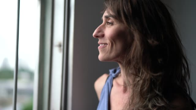 beautiful mature woman looking out of window - looking at view stock videos & royalty-free footage