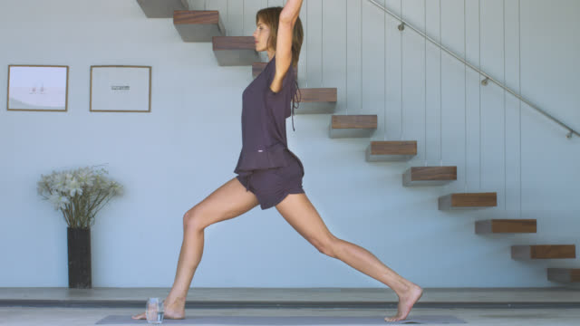 beautiful mature woman practising standing yoga poses. - home workout stock videos & royalty-free footage