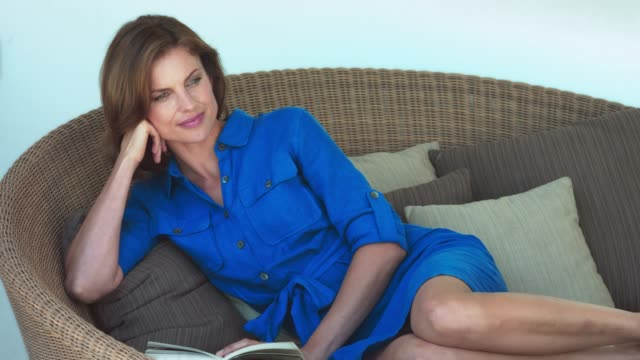 beautiful mature woman relaxing with a book. - person sitting cross legged stock videos & royalty-free footage