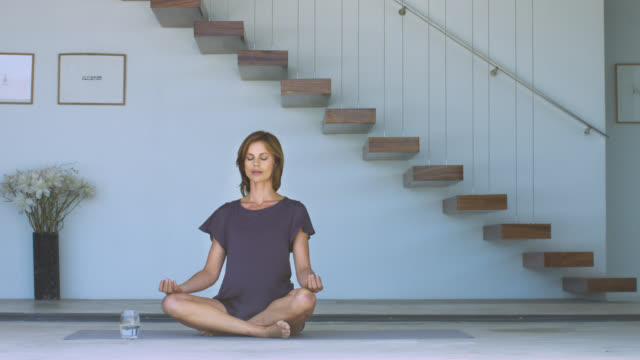 beautiful mature woman sitting calmly on a yoga mat. - cross legged stock videos & royalty-free footage