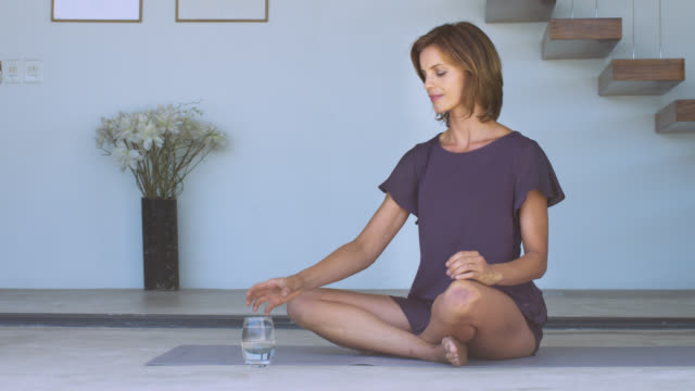 beautiful mature woman sitting on a yoga mat, focusing on her breathing then having a drink of water. - woman cross legged stock videos & royalty-free footage