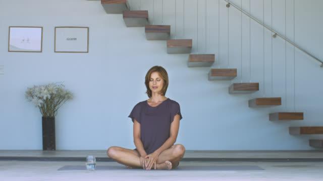 beautiful mature woman sitting on a yoga mat. - woman cross legged stock videos & royalty-free footage