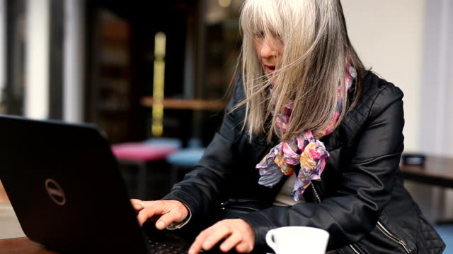 beautiful mature woman using laptop in cafe - satisfaction stock videos and b-roll footage