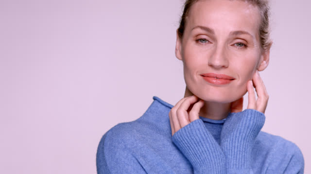vídeos de stock e filmes b-roll de beautiful mature woman wearing a blue jumper. - mulheres maduras