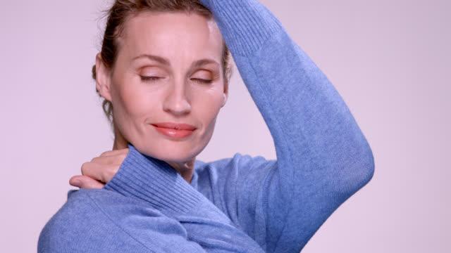 vidéos et rushes de beautiful mature woman wearing a soft blue sweater. - une seule femme d'âge mûr