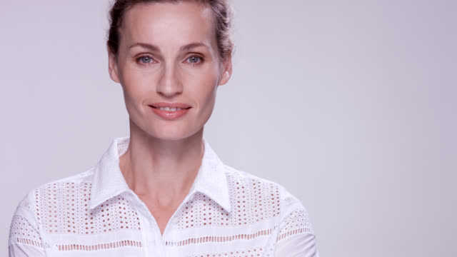 beautiful mature woman wearing a white shirt. - attraktive frau stock-videos und b-roll-filmmaterial