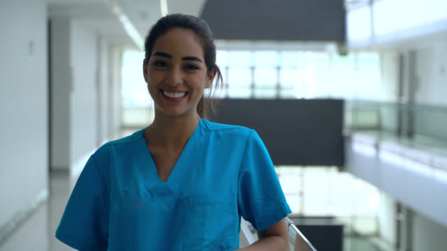 beautiful medical resident at the hospital smiling very cheerfully at camera - nurse stock videos & royalty-free footage